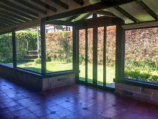 Un banco de madera sentado delante de la ventana en -