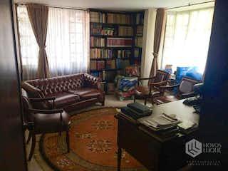 Una sala de estar llena de muebles y un estante de libros en -