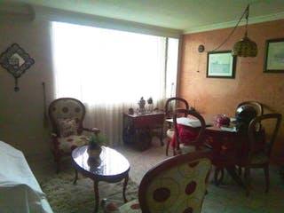 Una mujer sentada en una mesa en una sala de estar en Apartamento En Venta En Bogota Normandia