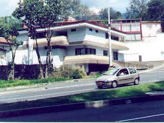 Un coche está estacionado delante de una casa en Casa-Local En Venta En Medellin Aguacatala