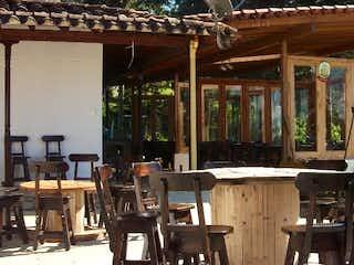 Una habitación llena de mesas y sillas de madera en Finca