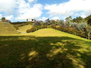 Una imagen de un campo con una torre de reloj en Lote En Venta En Envigado Alto De Las Palmas