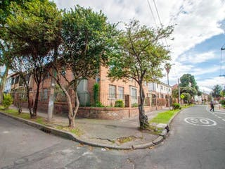 Una calle de la ciudad con un árbol y una calle en No aplica