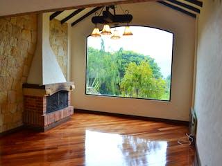 Una sala de estar con suelos de madera y una ventana en -