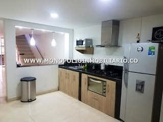 Una cocina con una estufa y un refrigerador en CASA UNIFAMILIAR EN VENTA - BARRIO TRINIDAD COD: 14416