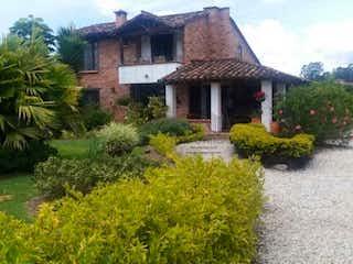 Una casa con un árbol y una casa en Casa en venta en Llanogrande de cuatro alcobas
