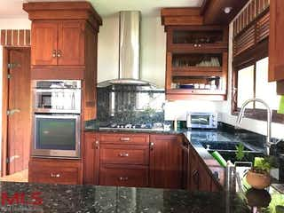 Una cocina con armarios de madera y electrodomésticos de acero inoxidable en Parcelación Leño Verde