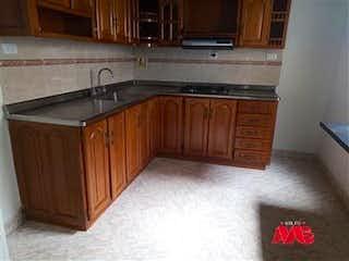 Una cocina con armarios de madera y un fregadero en Casa en venta en Cabañitas de 100m2.