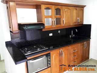 Una cocina con armarios de madera y electrodomésticos negros en Apartamento en venta en Villa Paula 3 Habitaciones.