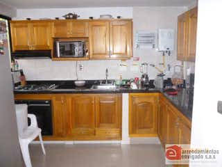 Cocina con armarios de madera y horno de microondas en PORTALEGRE