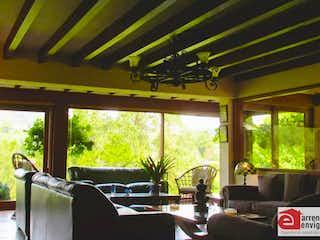 Una sala de estar llena de muebles y una gran ventana en Parcelación la Candelaria