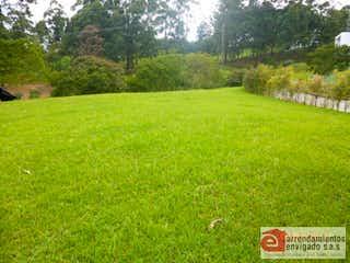 Una vista de un campo herboso con una señal de parada en el fondo en CERROVENTO