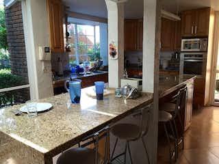 Una cocina con una mesa de comedor y sillas en Casa en venta en Colinas del Bosque de 426mt2 con terraza