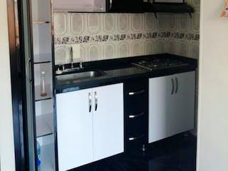 Una cocina con electrodomésticos de acero inoxidable y armarios blancos en Apartamento En Venta En Galicia, de 53mtrs2