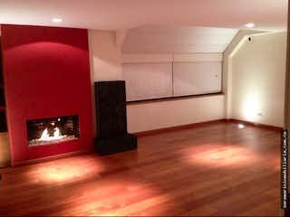 Una sala de estar llena de muebles y una chimenea en Casa en venta en Chicó Navarra de cuatro habitaciones