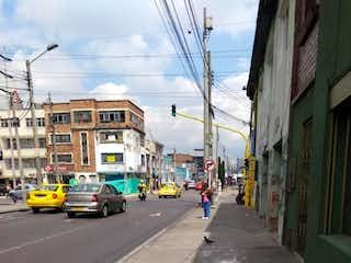 Una calle de la ciudad llena de coches y edificios estacionados en Casa-Local En venta En La Esperanza, Bogotá,