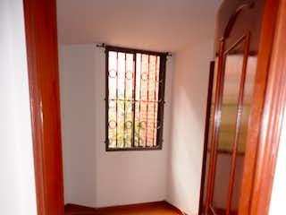 Una cama en una habitación con una puerta de madera en CONJUNTO RESIDENCIAL PARQUES DE POTOSI II