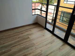 Un banco de madera sentado delante de la ventana en Conjunto Residencial Makagua