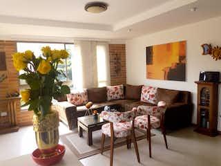 Una sala de estar llena de muebles y un jarrón de flores en Venta apartamento de 115 m2 en El Portal. Envigado