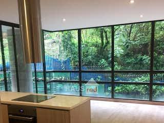 Una cocina con un gran ventanal y un suelo de madera en Vendo apartamento en rosales