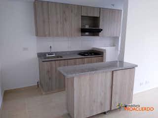 Una cocina con una estufa de fregadero y microondas en colina de asis