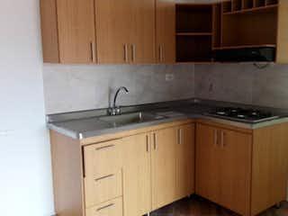 Una cocina con armarios de madera y un mostrador negro en Apartamento en venta en Rosales de  3 habtiaciones
