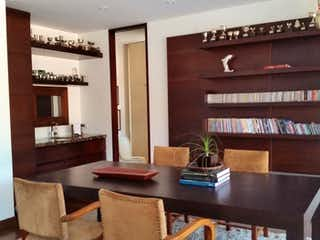 Una habitación llena de libros y un jarrón de flores en Bosques del Marques