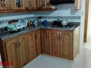 Una cocina con armarios de madera y electrodomésticos blancos en Otawa