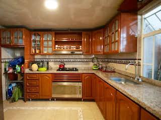 Una cocina con armarios de madera y un horno de cocina en Casa en venta en Barrio Santa Isabel, de 238,2mtrs2