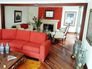 Una sala de estar llena de muebles y una chimenea en Casa En Venta En Bogota Alhambra cuenta con patio y 2 garajes cubiertos.