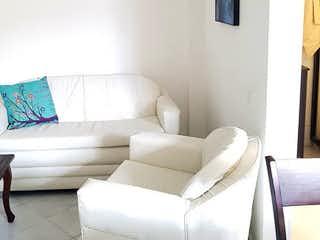 Un sofá blanco sentado en una sala de estar junto a una ventana en La 43