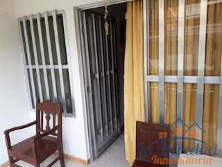 Una mecedora de madera sentada delante de la ventana en Apartamento ParaVenta,