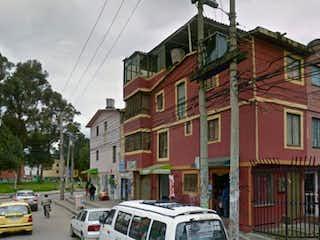Una calle de la ciudad con coches estacionados en ella en Casa en Bogota Tibabuyes - cuatro alcobas