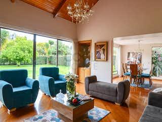 Una sala de estar llena de muebles y una gran ventana en Casa en venta en Guaymaral de 320m2