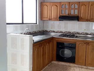 Una cocina con armarios de madera y un microondas negro en Casa en venta en Belén Centro, de 150mtrs2