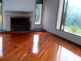 Una sala de estar con suelos de madera y una ventana en VEREDA EL HATO