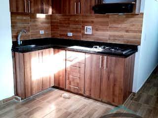 Una cocina de madera con suelos de madera y armarios de madera en EDIFICIO DAVILA