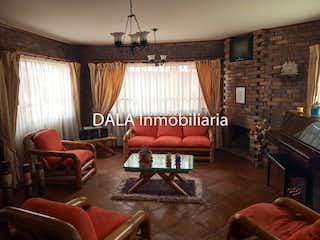Una sala de estar llena de muebles y una chimenea en SE VENDE CASA EN CAJICA CUNDINAMARCA .