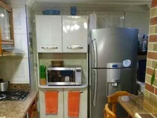 Una cocina con una estufa y un refrigerador en PRADOS DE VILLA NUEVA