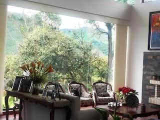 Un jarrón con flores en la parte superior de la mesa en Casa en la Calera Km 4 Vía a La Calera, con huerta, árboles frutales y dos terrazas.