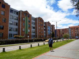 Un hombre caminando por una acera junto a edificios altos en Conjunto Plazuelas Del Hipodromo