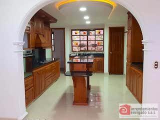 Una cocina con suelos de madera y armarios de madera en QUINTAS DE GUADARRAMA