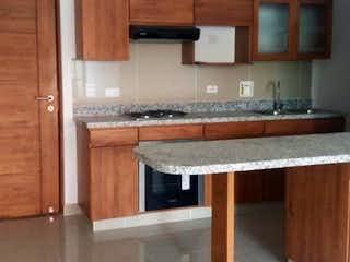 Una cocina con armarios de madera y una mesa de madera en URB SALTAMONTES