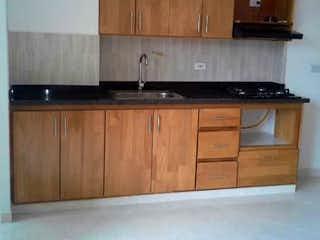 Una cocina con armarios de madera y electrodomésticos blancos en Apartamento en venta en Casco Urbano Caldas, de 62mtrs2