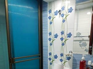 Un inodoro blanco sentado en un cuarto de baño junto a una ducha en Conjunto