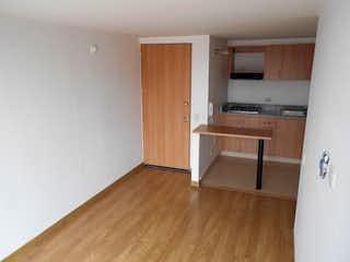 Una cocina con suelos de madera y armarios de madera en Edificio