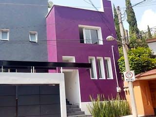 Un edificio rosado con una flor rosa en el costado en EXCELENTE CASA TOTALMENTE REMODELADA , PARA VIVIR DE LUJO
