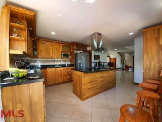 Una cocina con suelos de madera y armarios de madera en El Paraiso