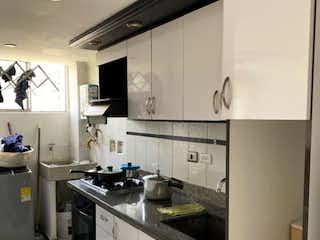 Una cocina con una estufa de fregadero y nevera en Apartamento en venta en Bello Horizonte de tres alcobas
