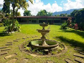 Una boca de incendios verde y blanca en un campo en Propiedad en Venta - Vereda El Totumo Girardota